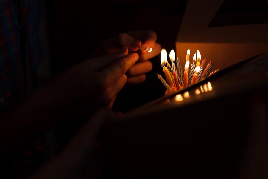 Harrison lights candles for Miranda's birthday.